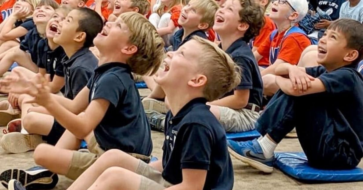 Private elementary school students laughing in assembly